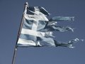 Old and torn flag of greece fluttering in the wind posted signs on a rusty pole Stock Images
