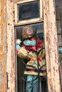 The old toy puppet in the old window there is an doll dirty with wood frame and bars house center of moscow Royalty Free Stock Photo