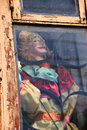 The old toy puppet in the old window there is an doll dirty with wood frame and bars house center of moscow Royalty Free Stock Images
