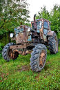 Old tractor against trees Royalty Free Stock Photography