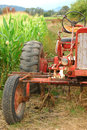Old tractor and corn in front of field soon to be a halloween maze Royalty Free Stock Photo