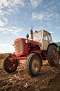 Old tractor in field against a cloudy sky Royalty Free Stock Photography