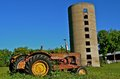 Old tractors and silo several very are parked to a vintage poured concrete Royalty Free Stock Images