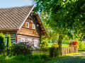 Old traditional timbered cottage with romantic and idyllic lush green flower garden with wooden fence on sunny summer Royalty Free Stock Photo