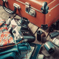 Old travel suitcase, sneakers, clothing and retro camera Royalty Free Stock Photo