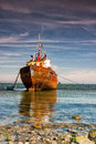 Old trawler on the empty beach in rumpside in england Stock Photo