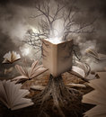 Old tree reading story book a with roots is a with books floating around it on a brown landscape Royalty Free Stock Image