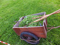 Old truck with mown grass with a scythe rake and whetstone on green meadow Royalty Free Stock Image