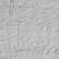 Old uneven brick wall with white painted plaster background texture closeup Royalty Free Stock Photography