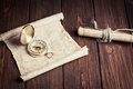 Old unrolled map rolled and compass on wooden table Stock Photography