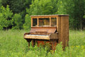 Old Upright Piano Abandoned in a Green Field Royalty Free Stock Photo