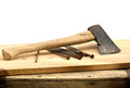 Old used ax hatchet with nails on the wooden desk Stock Photo