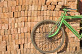 Old used bicycle near red bricks stack, India Royalty Free Stock Photo