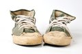 Old used green sneakers on white background Stock Images