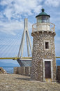 Old versus new an lighthouse in front of the cable bridge between rio and atirrio patra greece Royalty Free Stock Image