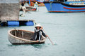 Old Vietnamese woman paddles a boat in the ocean Royalty Free Stock Image