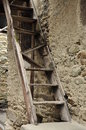 Old village broken wood ladder and stone wall Royalty Free Stock Photo