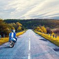 Old vintage blue scooter on the background of the road receding into the distance. Beautiful landscape. Cloudy sky Royalty Free Stock Photo