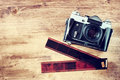 Old vintage camera and film strips over wooden brown background Royalty Free Stock Photo