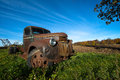 Old vintage farm truck landscape scene of an in the background is a blue sky Stock Image