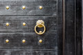 Old vintage massive wooden black door with metal locker and hand Royalty Free Stock Photo