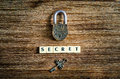 Old vintage padlock and key with secret sign on wooden texture Stock Image