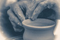 Old vintage photo. The potter molds clay jug pot