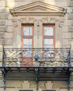 Old vintage retro balcony with columns and ornaments on an old building with windows on one of the streets of Lviv, Ukraine Royalty Free Stock Photo