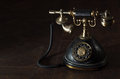Old vintage rotary phone or antique with a handset and cradle on a dark shadowed background with copyspace Royalty Free Stock Photography