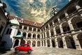 Old vintage small red car in historical scene. Klagenfurt ancient building