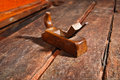 Old vintage smoothing plane angle two wood crafting tool used to smooth boards placed on an weathered workbench Stock Photo