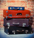 Old vintage suitcases isolated near brick wall Stock Photo