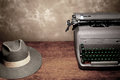 Old vintage typewriter reporter s fedora hat wooden table room copy Stock Photos