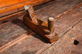 Old vintage wood smoothing plane crafting tool used to smooth boards placed on an weathered workbench Stock Photography