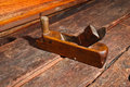Old vintage wood smoothing plane crafting tool used to smooth boards placed on an weathered workbench Royalty Free Stock Image