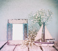 Old vintage wooden frame, white flowers and sailing boat on wooden table. vintage filtered image. nautical lifestyle concept Royalty Free Stock Photo