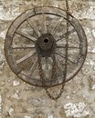 Old vintage wooden wheel with rusty metal chain hanging on a stone house wall Royalty Free Stock Photo