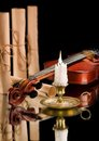 Old violin witn candle ond old scroll of paper Royalty Free Stock Photo