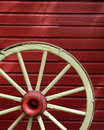 Old Wagon Wheel with Red Wall Stock Image