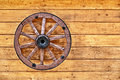 Old wagon wheel on a wooden wall Royalty Free Stock Photo