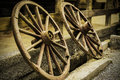 Old wagon wheels a couple of inclined and leaning against a fence on a farm Royalty Free Stock Photos