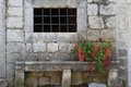 Old wall of the house with a window and a bench with flower pots Royalty Free Stock Images