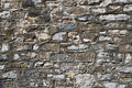Old wall of stone blocks ancient various with thick cement layer Stock Image