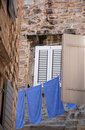 Old wall, window and blue linen (Italy) Stock Photos