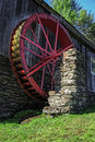 Old water powered grist mill an red wheel providing power to an in vermont Stock Photography
