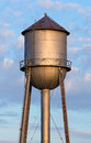 Old water tower tank an metal in the light of the morning sun stands tall against a cloudy blue sky in americas midwest Stock Photo