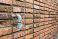 Old water tube woth the brick wall Royalty Free Stock Photo