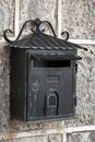 Old weathered black metal mailbox mounted on gray stone wall Stock Photos