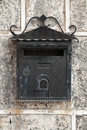 Old weathered black metal mailbox mounted on gray stone wall front view Stock Photography