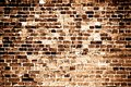 Old and weathered grungy red brick wall as texture background in sepia tone with some vignetting Royalty Free Stock Photo